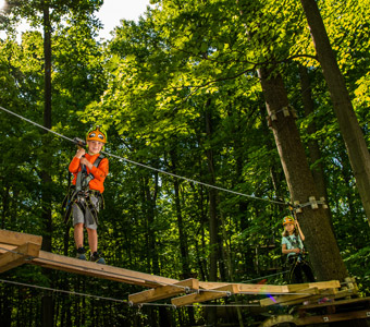 Two kids exploring the tree tops at Lake Erie Canopy Tours