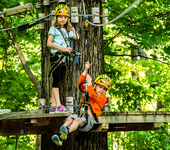One boy on a zipline while a girl waits on a wooden plank behind him