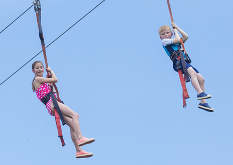 Two children playing on a zipline with a view from below