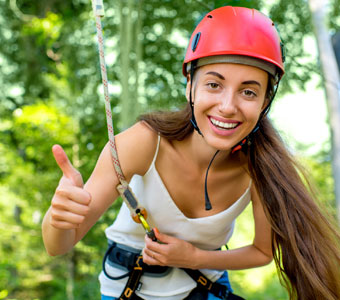 girl with a helmet on smiling and giving a thumbs up during a canopy tour