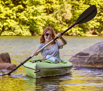 Girl wearing sunglasses in a green canoe on a lake