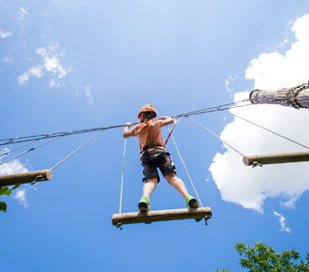 close up of a boy suspended in the air moving through a challenge course