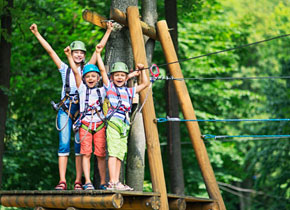 three kids smiling with their arms up proud to be completing an adventure course