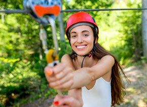 girl wearing a red helmet holding onto a carabiner to start ziplining