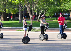 four people on a segway tour wearing helmets cruising through town